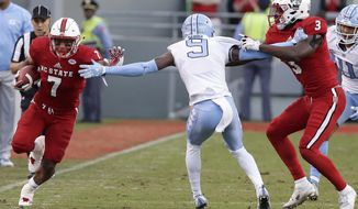 North Carolina cornerback K.J. Sails (9) is blocked by North Carolina State's Germaine Pratt (3) as North Carolina State running back Nyheim Hines (7) runs the ball during the first half of an NCAA college football game in Raleigh, N.C., Saturday, Nov. 25, 2017. (AP Photo/Gerry Broome)