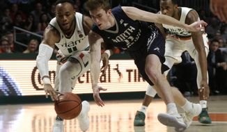 Miami's Bruce Brown Jr., left, and North Florida's Garrett Sams (11) go for the ball during the first half of an NCAA college basketball game, Saturday, Nov. 25, 2017, in Coral Gables, Fla. (AP Photo/Lynne Sladky)
