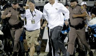 Central Florida coach Scott Frost, center, runs onto the field after the team defeated South Florida 49-42 in an NCAA college football game, Friday, Nov. 24, 2017, in Orlando, Fla. (AP Photo/John Raoux)