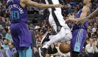San Antonio Spurs' Kyle Anderson, center, is fouled as he drives between Charlotte Hornets' Michael Carter-Williams, left, and Jeremy Lamb, right, during the first half of an NBA basketball game in Charlotte, N.C., Saturday, Nov. 25, 2017. (AP Photo/Chuck Burton)