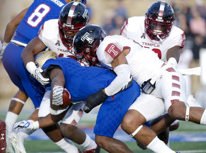 Tulsa's D'Angelo Brewer (4) is tackled by Temple defenders during the first half of an NCAA college football game Saturday, Nov. 25, 2017, in Tulsa, Okla. (Jessie Wardarski/Tulsa World via AP)