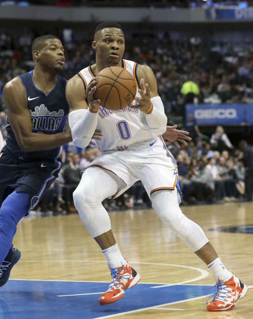 Oklahoma City Thunder guard Russell Westbrook (0) passes off the ball against Dallas Mavericks guard Dennis Smith Jr. during the first half of an NBA basketball game in Dallas, Saturday, Nov. 25, 2017. (AP Photo/LM Otero)