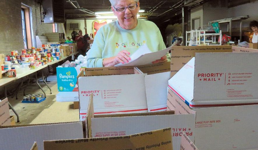 In this Nov. 4, 2017 photo, volunteer Sandra Kelly prepares boxes for shipment to U.S. military  personnel at the Support the Troops headquarters in Hartford, Wis. The charity organization founded by LeAnn Boudwine 11 years ago hopes to send their 10,000th care package by the end of the year.  (Jill Badzinski/West Bend Daily News via AP)