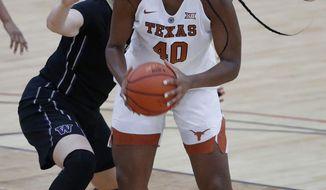 Texas' Jatarie White drives around Washington's Hannah Johnson during the first half of an NCAA basketball game, Saturday, Nov. 25, 2017, in Las Vegas. (AP Photo/John Locher)