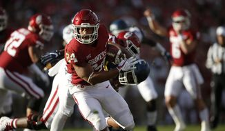 Oklahoma running back Rodney Anderson (24) runs for a touchdown against a West Virginia defender during an NCAA college football game in Norman, Okla., Saturday, Nov. 25, 2017. (Ian Maule/Tulsa World via AP)