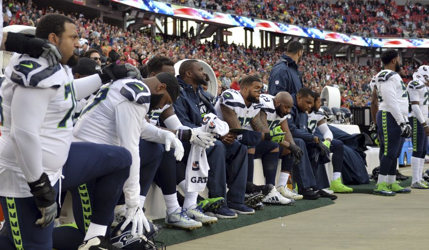 Seattle Seahawks players listen to the national anthem before an NFL football game against the San Francisco 49ers Sunday, Nov. 26, 2017, in Santa Clara, Calif. (AP Photo/Don Feria)