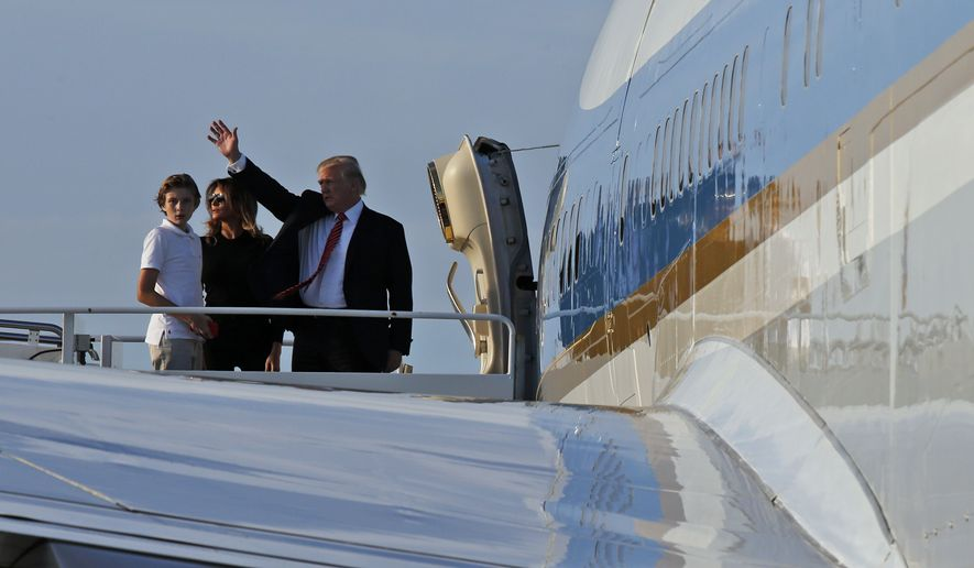 President Donald Trump waves as he boards Air Force One with first lady Melania Trump, and Barron Trump, 11, at the Palm Beach International Airport, Sunday, Nov. 26, 2017, in West Palm Beach, Fla. Trump is returning to Washington after spending Thanksgiving at his Mar-a-Lago resort. (AP Photo/Alex Brandon)