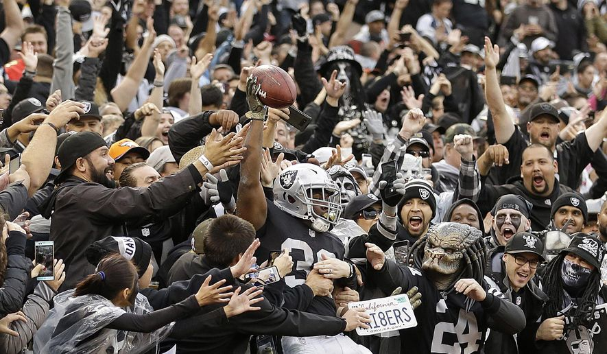 Oakland Raiders running back Jalen Richard (30) celebrates with fans after scoring a touchdown against the Denver Broncos during the second half of an NFL football game in Oakland, Calif., Sunday, Nov. 26, 2017. (AP Photo/Ben Margot)