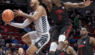 Connecticut guard Jalen Adams, left, shoots past Arkansas forward Adrio Bailey (2) during the first half of an NCAA college basketball game in the Phil Knight Invitational tournament in Portland, Ore., Sunday, Nov. 26, 2017. (AP Photo/Craig Mitchelldyer)