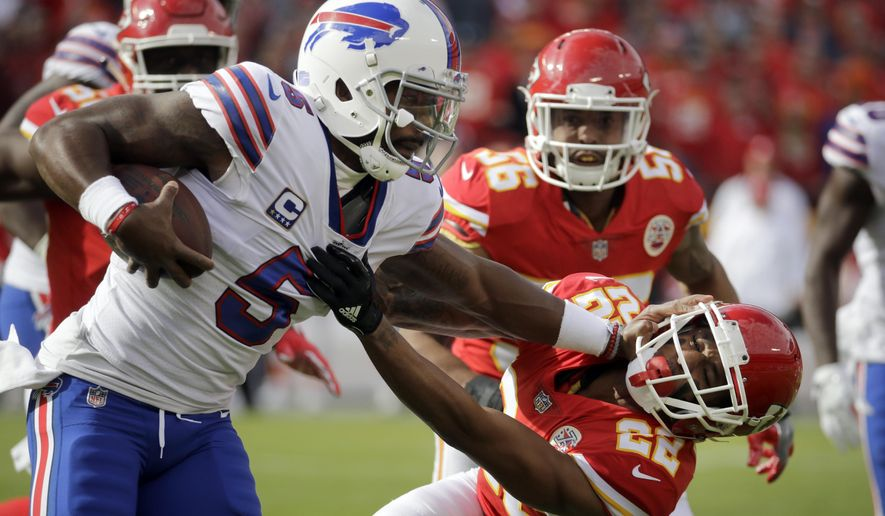 Buffalo Bills quarterback Tyrod Taylor (5) stiff-arms Kansas City Chiefs defensive back Marcus Peters (22) during the first half of an NFL football game in Kansas City, Mo., Sunday, Nov. 26, 2017. (AP Photo/Charlie Riedel)
