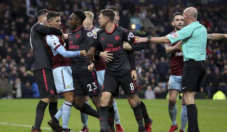 Burnley's Matthew Lowton, second left and Arsenal's Aaron Ramsey react, during the English Premier League soccer match between Burnley and Arsenal, at Turf Moor, in Burnley, England, Sunday Nov. 26, 2017. (Martin Rickett/PA via AP)