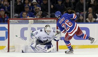 New York Rangers' Jimmy Vesey, right, scores the winning goal past Vancouver Canucks goalie Jacob Markstrom during a shootout at an NHL hockey game, Sunday, Nov. 26, 2017, in New York. (AP Photo/Seth Wenig)