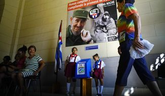 Back-dropped by a poster showing the late Fidel Castro, a woman arrives to a polling station to vote for municipal elections in Havana, Cuba, Sunday Nov. 26, 2017. The elections were postponed by a month to Nov. 26 after Hurricane Irma devastated part of the island last September.(AP Photo/Ramon Espinosa)