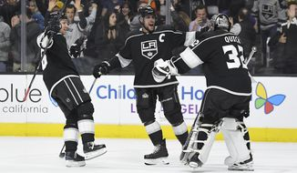 Los Angeles Kings goalie Jonathan Quick, right, celebrates with left wing Jussi Jokinen, left, of Finland, and center Anze Kopitar, of Slovenia, after the Kings defeated the Anaheim Ducks 2-1 in an overtime shootout of an NHL hockey game, Saturday, Nov. 25, 2017, in Los Angeles. (AP Photo/Mark J. Terrill)