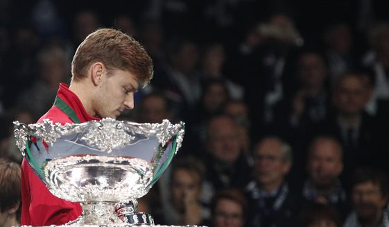 Belgium's David Goffin walks past the cup after France won the Davis Cup at the Pierre Mauroy stadium in Lille, northern France, Sunday, Nov.26, 2017. France won the Davis Cup for the first time in 16 years after beating Belgium 3-2. (AP Photo/Christophe Ena)