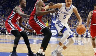 Kentucky's Kevin Knox (5) looks for an opening on Illinois-Chicago's Tai Odiase, middle, and Dikembe Dixson (10) during the first half of an NCAA college basketball game, Sunday, Nov. 26, 2017, in Lexington, Ky. (AP Photo/James Crisp)