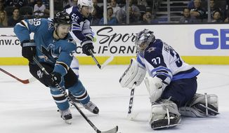 San Jose Sharks center Logan Couture (39) scores a goal past Winnipeg Jets goalie Connor Hellebuyck (37) during the second period of an NHL hockey game in San Jose, Calif., Saturday, Nov. 25, 2017. (AP Photo/Jeff Chiu)
