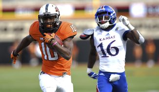 Kansas corner back Kyle Mayberry (16) chases after Oklahoma St wide receiver Tyrell Alexander (10) during his 56 yard run to the Kansas 1 during the fourth quarter of a NCAA college football game between Kansas and Oklahoma St in Stillwater, Okla., Saturday, Nov. 25, 2017. Oklahoma St scored in the subsequent series, adding the final touchdown to a 58-17 win over Kansas. (AP Photo/Brody Schmidt)