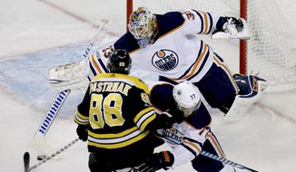 Edmonton Oilers goalie Cam Talbot (33) makes a stick save as defenseman Oscar Klefbom (77) holds off Boston Bruins right wing David Pastrnak (88) during the third period of an NHL hockey game in Boston, Sunday, Nov. 26, 2017. (AP Photo/Mary Schwalm)
