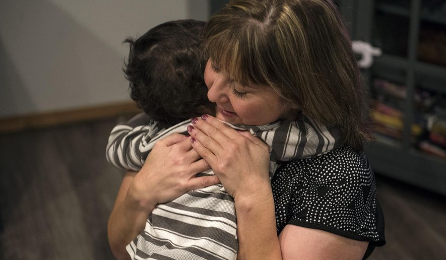 """Sheryl Herd hugs her son Karter, 2, as they play in the living room after breakfast at their home in Vancouver, Wash., on Wednesday, Nov. 15, 2017. Karter's adoption was finalized earlier this month. """"I just wish I could encourage more people to do it,"""" Herd said. (Alisha Jucevic/The Columbian via AP)"""