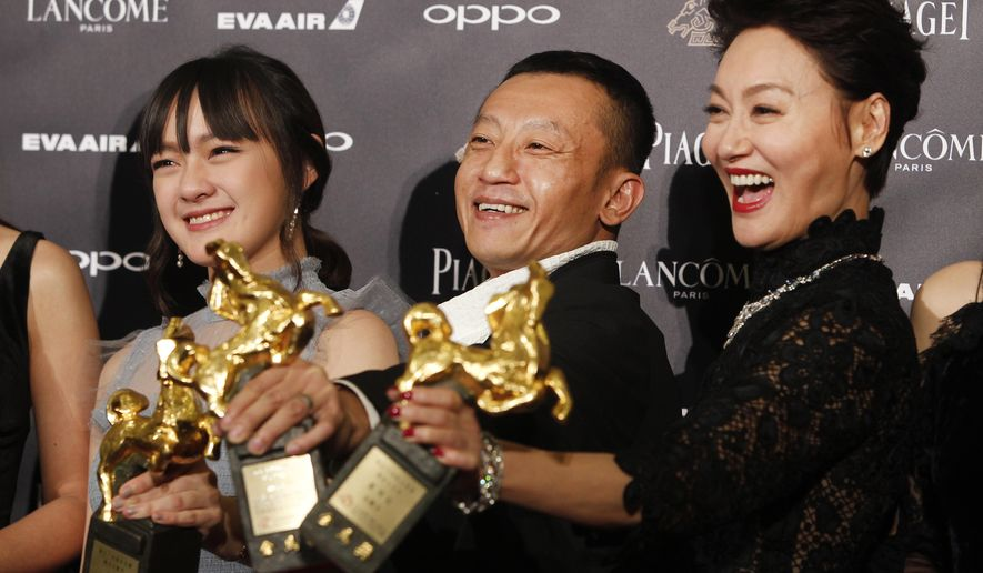 """Taiwanese actress Vicky Chen, from left, director Yang Ya Che and Hong Kong actress Kara Wai hold their awards for Best Supporting Actress, Best Feature Film and Best Leading Actress at the 54th Golden Horse Awards in Taipei, Taiwan, Saturday, Nov. 25, 2017. They won for the film """" The Bold, The Corrupt, and The Beautiful """" at this year's Golden Horse Awards -the Chinese-language film industry's biggest annual events.(AP Photo/ Chiang Ying-ying)"""