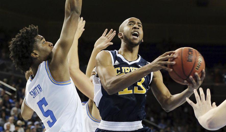 University of California Irvine forward Brandon Smith (13) drives as UCLA guard Chris Smith (5 ...
