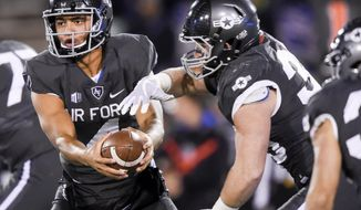 Air Force quarterback Isaiah Sanders fakes a handoff to running back Timothy McVey (33) during an NCAA college football game against Utah State at Air Force Academy, Colo., Saturday, Nov. 25, 2017. (Dougal Brownlie/The Gazette via AP)