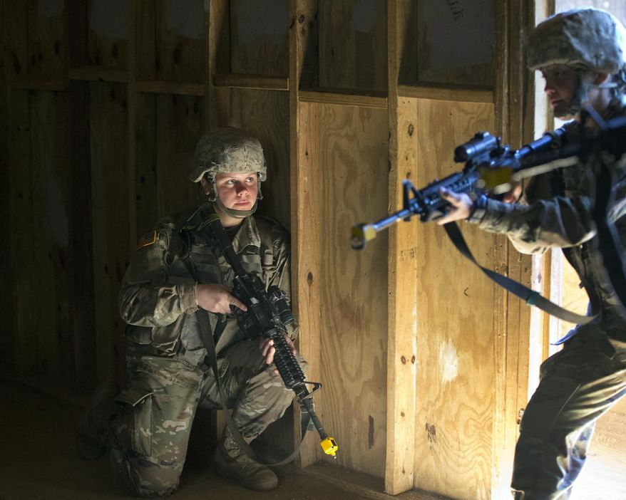 In this Oct. 4, 2017, photo, U.S. Army recruit Kirsten practices building clearing tactics with male recruits at Ft. Benning, Ga. She is one of a handful of women training to become infantry soldiers. The Army's introduction of women into the infantry has moved steadily but cautiously this year. As home to the previously all-male infantry and armor schools, Fort Benning had to make a number of adjustments, including female dorm rooms, security cameras, monitoring stations. (AP Photo/John Bazemore)