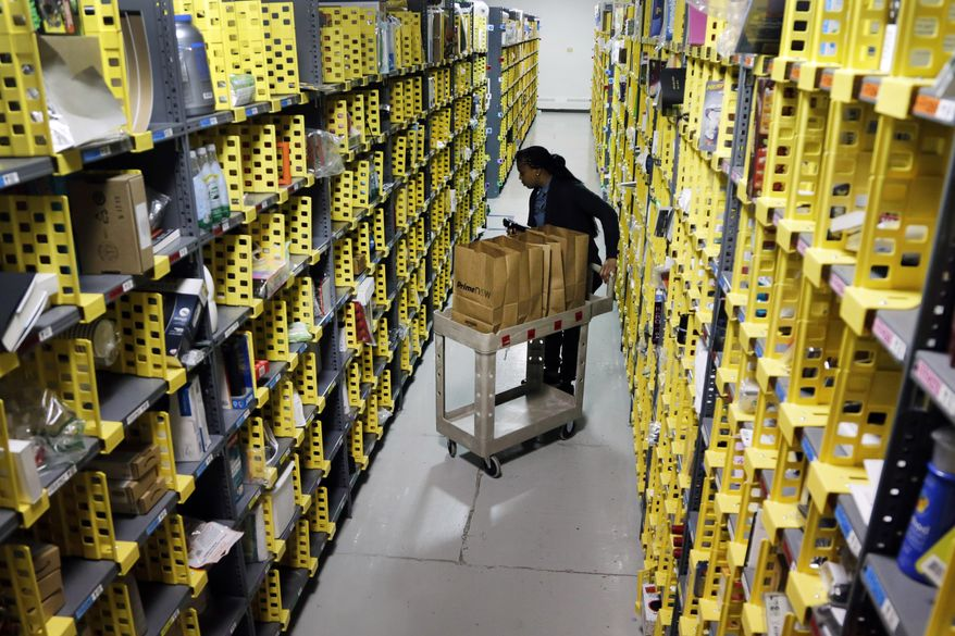 In this Tuesday, Dec. 22, 2015, file photo, Amazon Prime employee Alicia Jackson hunts for items at the company's urban fulfillment facility that have been ordered by customers, in New York. Shoppers are expected to spend $6.6 billion on Cyber Monday, Nov. 27, 2017, up more than 16 percent from a year ago, according to Adobe Analytics, the research arm of software maker Adobe. And more people will be picking up their phones to shop: Web traffic from smartphones and tablets is expected to top desktop computers for the first time this year, Adobe said. (AP Photo/Mark Lennihan, File)