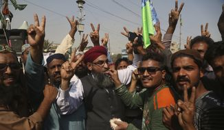 Supporters of the radical religious party, Tehreek-i-Labaik Ya Rasool Allah celebrate after the country's Law Minister Zahid Hamid's resignation, during a sit-in protest in Karachi, Pakistan, Monday, Nov. 27, 2017. Pakistani Islamists announced they were disbanding their sit-in near Islamabad after the country's law minister resigned, caving in to the protesters who have been demanding his ouster in a three-week-long rally. (AP Photo/Shakil Adil)