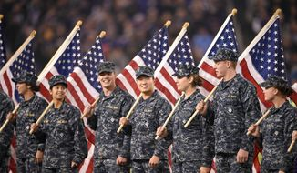 Members of the U.S. Navy hold American flags before an NFL football game between the Baltimore Ravens and the Houston Texans, Monday, Nov. 27, 2017, in Baltimore. (AP Photo/Nick Wass)