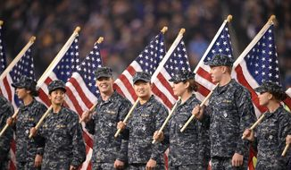 Members of the U.S. Navy hold American flags before an NFL football game between the Baltimore Ravens and the Houston Texans, Monday, Nov. 27, 2017, in Baltimore. (AP Photo/Nick Wass) **FILE**