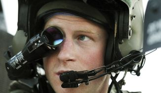 FILE - In this Dec. 12, 2012 file photo Britain's Prince Harry or just plain Captain Wales as he is known in the British Army, wears his monocle gun sight as he sits in the front seat of his cockpit at the British controlled flight-line in Camp Bastion southern Afghanistan. Palace officials announced Monday Nov. 27, 2017, Prince Harry and Meghan Markle are engaged, and will marry in the spring. (AP Photo/ John Stillwell, File)