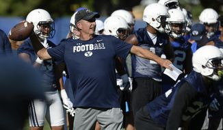"FILE - In this July 27, 2017, file photo, BYU football offensive coordinator and quarterbacks coach Ty Detmer works with the team during NCAA college football practice in Provo, Utah. Ty Detmer is no longer the offensive coordinator at BYU. The school announced Monday, Nov. 27, 2017, that the Heisman Trophy winner ""has been relieved of his role as the team's offensive coordinator.""(Francisco Kjolseth/The Salt Lake Tribune via AP, File)"