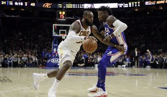 Cleveland Cavaliers' LeBron James, left, dribbles past Philadelphia 76ers' Robert Covington during the first half of an NBA basketball game, Monday, Nov. 27, 2017, in Philadelphia. (AP Photo/Matt Slocum)