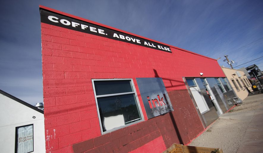 """The Ink! coffee shop is shown after graffiti was erased from the walls of the building in the River North Art district Monday, Nov. 27, 2017, in Denver. The shop, which is part of a Colorado chain, has been in the eye of a storm of outrage from neighbors after putting up a sidewalk sign that said the owners were """"happily gentrifying"""" the area, a transformation that has forced many of the former residents and businesses to move out and make way for salons, pilates studios and brew pubs. (AP Photo/David Zalubowski)"""