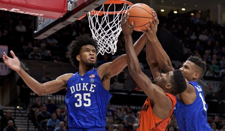 Duke forward Marvin Bagley III, left, Duke forward Javin DeLaurier, right and Florida forward Kevarrius Hayes, center, fight for a rebound during the second half of an NCAA college basketball game in the Phil Knight Invitational tournament in Portland, Ore., Sunday, Nov. 26, 2017. (AP Photo/Craig Mitchelldyer)