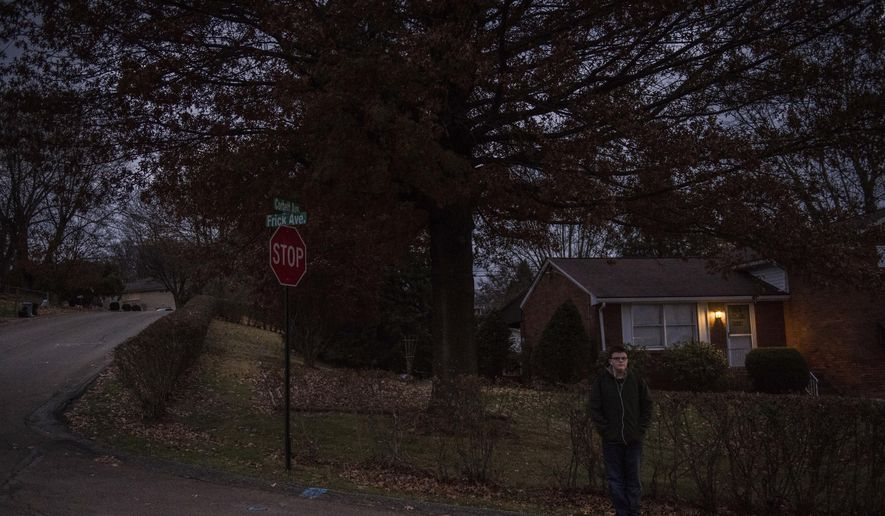 In this Friday, Nov. 17, 2017, photo, Seth Weston, a ninth grader at Hempfield Area High School, waits for the bus at Frick and Corbett Avenues in Hempfield Township, Pa. School districts in and around Pittsburgh, including some whose first bell rings at 7 a.m., are evaluating daily schedules as research and day-to-day experience make it increasingly clear that later start times could benefit students' mental health and academic success. (Dan Speicher/Pittsburgh Tribune-Review via AP)