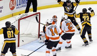 Pittsburgh Penguins' Sidney Crosby (87) celebrates scoring the game-winning goal in overtime past Philadelphia Flyers goalie Brian Elliott (37) during an NHL hockey game in Pittsburgh, Monday, Nov. 27, 2017. The Penguins won 5-4. (AP Photo/Gene J. Puskar)