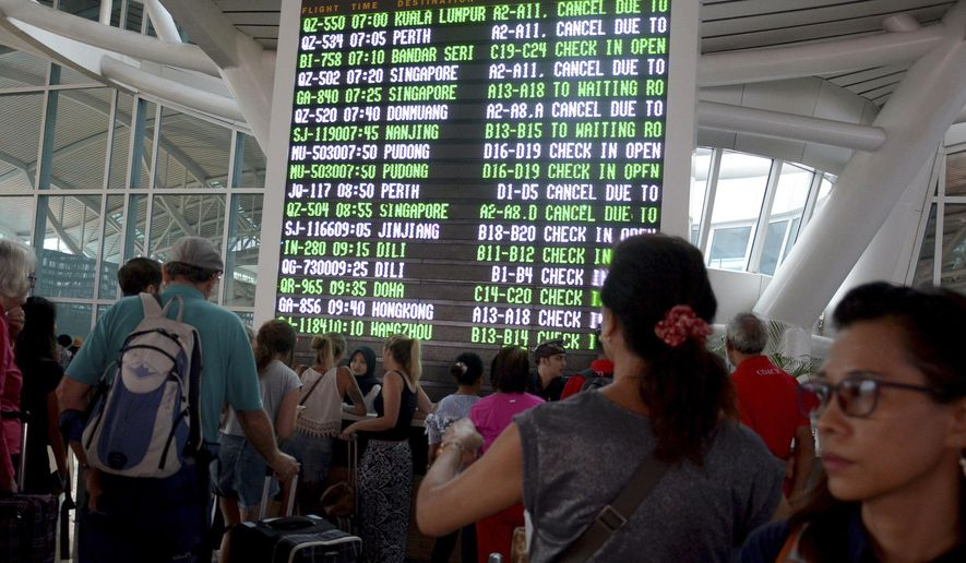 A flight information board shows cancelled flights at Ngurah Rai International Airport in Bali, Indonesia, Monday, Nov. 27, 2017. Indonesian authorities raised the alert for a rumbling volcano on Bali to the highest level on Monday, stranding tens of thousands of travelers as ash clouds forced the closure of the tourist island's international airport. (AP Photo/Ketut Nataan)