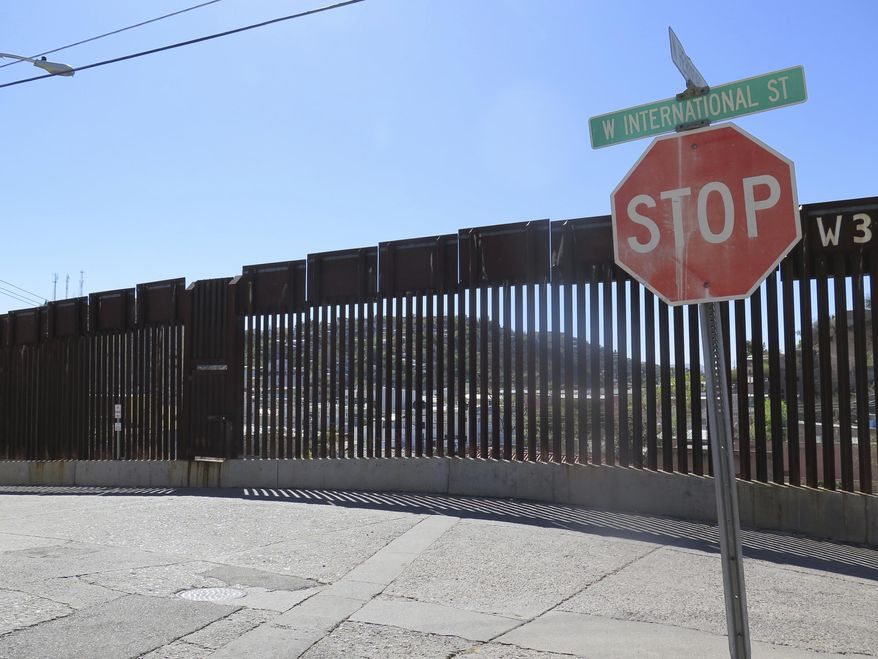 FILE - This March 9, 2016, file photo, shows a stop sign in front of the international border fence in Nogales, Ariz. Reports that a group of Middle Eastern men had been caught crossing the border illegally from Mexico into Arizona two years ago set off alarms among right-wing blogs and for Arizona Gov. Doug Ducey. Now, documents obtained by The Associated Press through a public records request reveal that not only were the men cleared of any ties to terrorism, but they were badly mistreated by two Mexican smugglers with a history of crossing the border illegally. (AP Photo/Astrid Galvan, File)