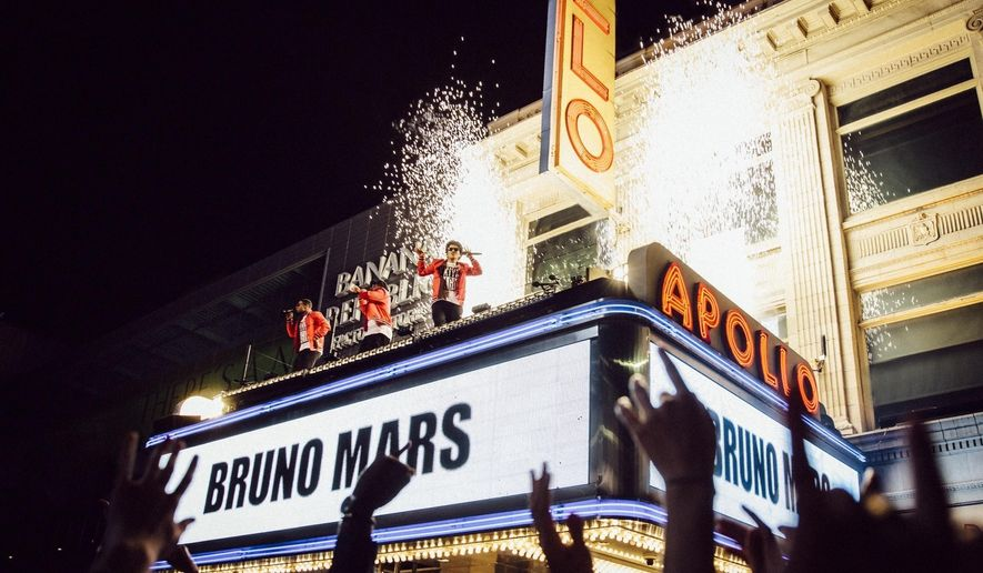 """This image released by CBS shows Bruno Mars, center, during the taping a TV special,  """"BRUNO MARS: 24K MAGIC LIVE AT THE APOLLO,"""" on top of the Apollo Theater marquee in New York. The special will air Nov. 29 on CBS. (CBS via AP)"""