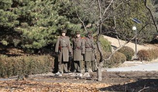 Three North Korean soldiers look at the South side at the spot where a North Korean soldier crossed the border on Nov. 13, 2017, at the Panmunjom in the Demilitarized Zone, South Korea, Monday, Nov. 27, 2017. South Korea is reportedly broadcasting into North Korea news of the recent escape of the North Korean soldier over the rivals' border as part of its psychological warfare against the North. (AP Photo/Lee Jin-man) ** FILE **