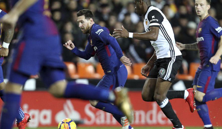 Barcelona's Lionel Messi, centre controls the ball away from Valencia's Kondogbia, right, during the Spanish La Liga soccer match between Valencia and FC Barcelona at the Mestalla stadium in Valencia, Spain, Sunday, Nov. 26, 2017. (AP Photo/Alberto Saiz)