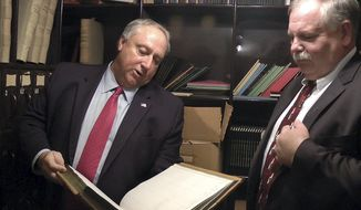 Terry Pfaff, left, chief of staff, New Hampshire House of Representatives, inspects a book found in a vault at the Statehouse, Monday, Nov. 27, 2017, in Concord, N.H. Beside him is House Speaker Shawn Jasper, right. The vault, which had been locked for decades in a room that once served as the state treasury in the 1800s, is now assigned to the Senate Finance Committee. (AP Photo/Holly Ramer)