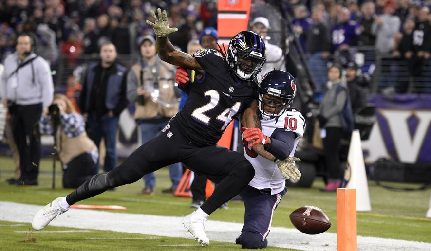 Baltimore Ravens cornerback Brandon Carr (24) breaks up a pass attempt to Houston Texans wide receiver DeAndre Hopkins in the first half of an NFL football game, Monday, Nov. 27, 2017, in Baltimore. (AP Photo/Nick Wass)