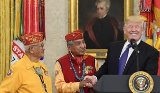 President Donald Trump, right, meets with Navajo Code Talkers Peter MacDonald, center, and Thomas Begay, left, in the Oval Office of the White House in Washington, Monday, Nov. 27, 2017. (AP Photo/Susan Walsh)
