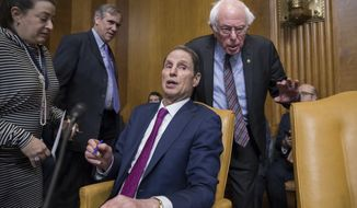 Sen. Ron Wyden, D-Ore., center, is flanked by Sen. Jeff Merkley, D-Ore., left rear, and Sen. Bernie Sanders, I-Vt., as the Senate Budget Committee met to work on the Republican tax bill, on Capitol Hill in Washington, Tuesday, Nov. 28, 2017. (AP Photo/J. Scott Applewhite)