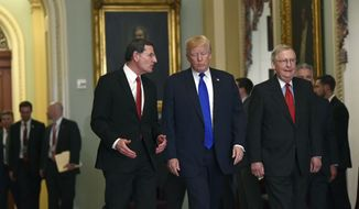 President Donald Trump, center, walks with Sen. John Barrasso, R-Wyo., left, and Senate Majority Leader Mitch McConnell of Ky., right, as he arrives on Capitol Hill in Washington, Tuesday, Nov. 28, 2017. (AP Photo/Susan Walsh)