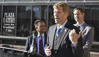 Albuquerque Mayor-elect Tim Keller, center, speaks outside of City Hall, Tuesday, Nov. 28, 2017, during a press conference about the future of the police department in Albuquerque, N.M. Keller named a team that will oversee the transition of law enforcement in New Mexico's largest city as he prepares to take office. (AP Photo/Russell Contreras)